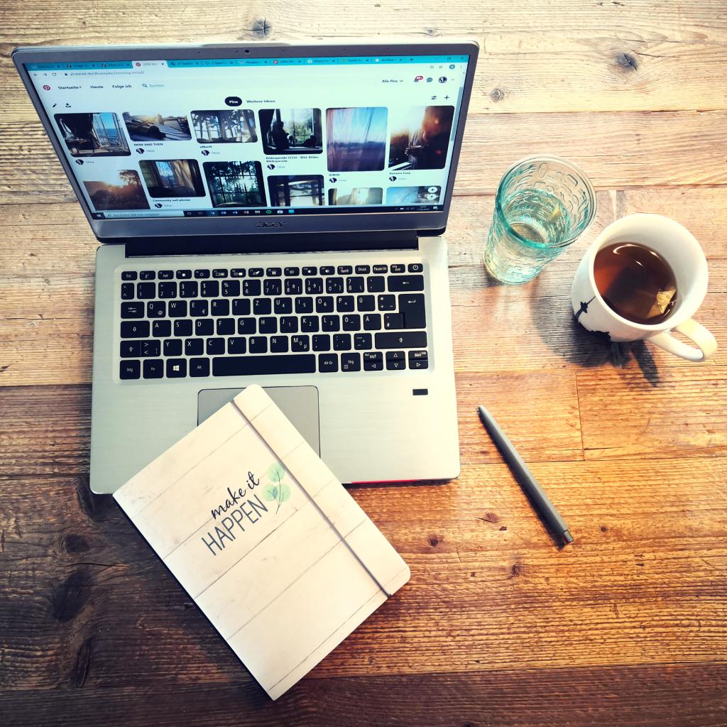 Produktivität steigern am Arbeitsplatz: Laptop, Notizbuch, Getränke