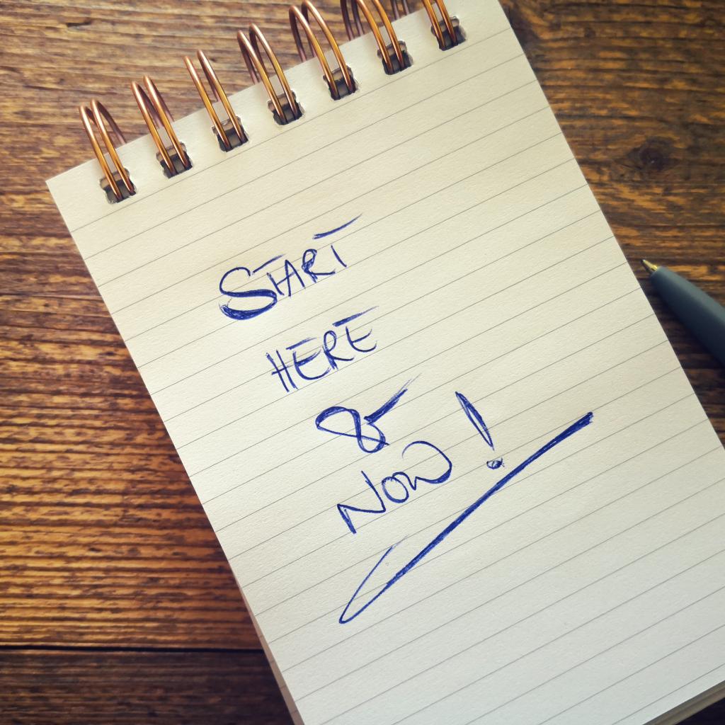 """Notizblock, auf rustikalem Holztisch . Motivation durch die Aussage """"start here & now"""""""
