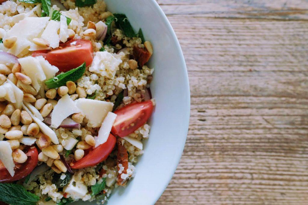 bunter, frischer Sommer-Quinoa-Salat mit leckeren Zutaten unkompliziert zubereitet, auf einem rustikalen Holztisch