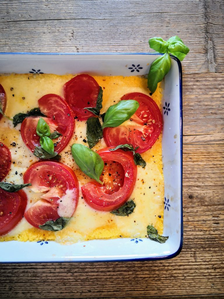 Polenta-Pizza Caprese, glutenfrei und lecker in der Ofenform, angerichtet mit frischem Basilikum