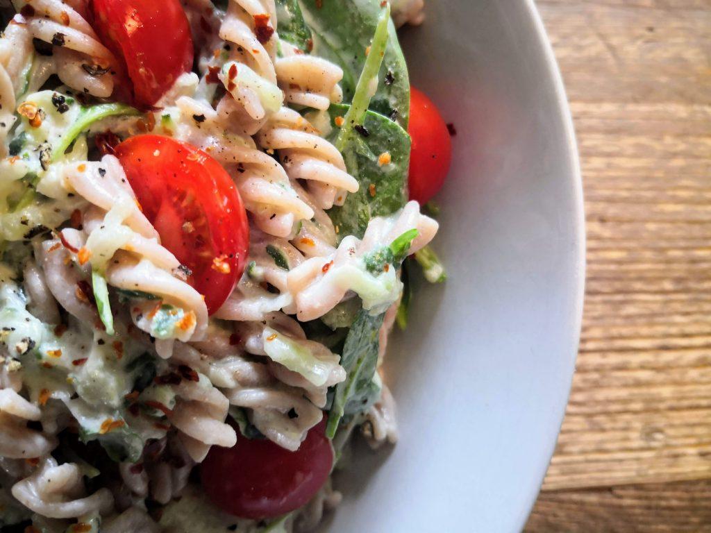 """Sommerlicher Pasta Salat """"Tzatziki Style"""" auf einem rustikalen Holztisch"""